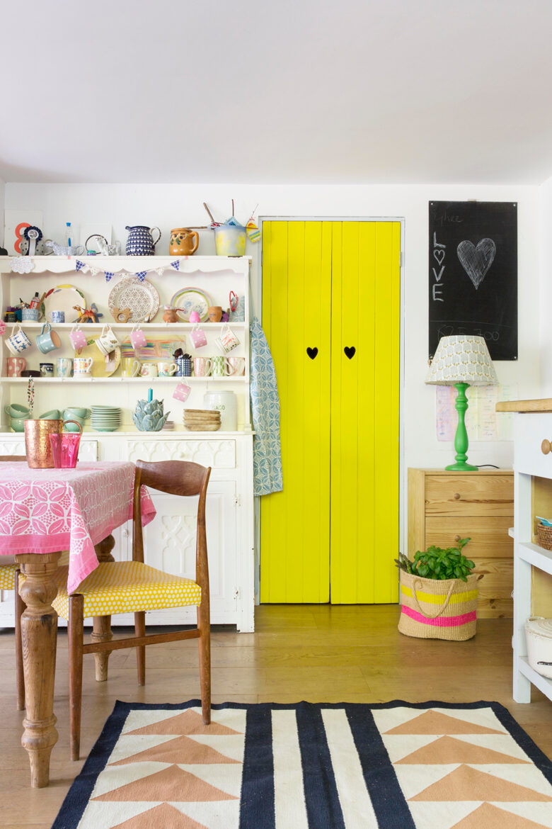Bright yellow door, geometric print rug and dresser in the colourful kitchen of designer and block print-maker Molly Mahon at her home in Ashdown Forest, East Sussex
