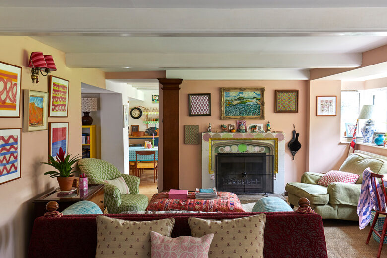 Pink living room with colourful art and Charleston-inspired fireplace at the home of designer and hand block print-maker Molly Mahon in Ashdown Forest, East Sussex
