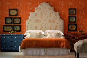 Orange painted wallpaper in 'Wychwood' designed by decorative artist Melissa White for the Kit Kemp collection for Andrew Martin in a bedroom with a beautiful headboard, painted furniture and antiques